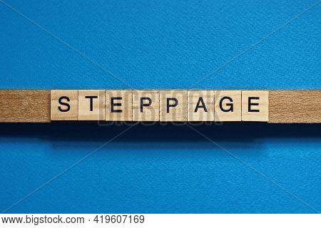 Gray Word Steppage In Small Square Wooden Letters With Black Font On A Blue Background