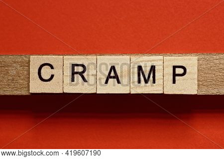 Text The Word Cramp From Gray Wooden Small Letters With Black Font On An Red Table