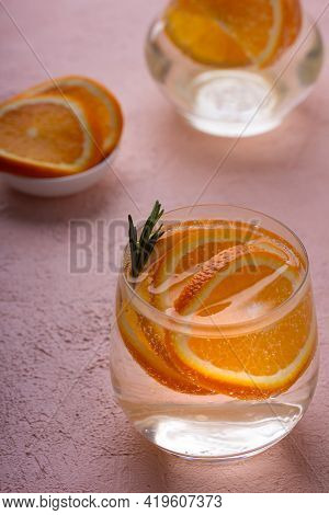 Refreshing Detox Lemonade With Sliced Orange And A Sprig Of Rosemary On A Pink Table. Refreshing Sum