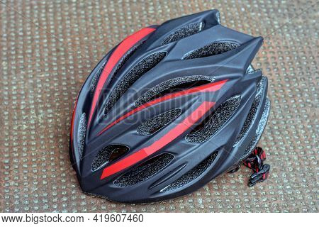 One Large Black Plastic Bicycle Helmet With Red Stripes Lying On A Brown Table