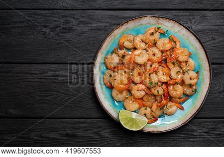 Prawns Fried With Garlic On A Blue Porcelain Plate With A Slice Of Lime On A Black Wooden Table. Top