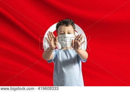 Little White Boy In A Protective Mask On The Background Of The Flag Of Tunisia. Makes A Stop Sign Wi