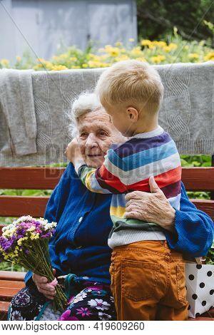 90 Year Old Great-grandmother, Grandmother With Grandson Together. Grandson Hugs His Beloved Grandmo