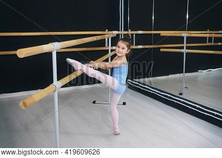 Little Girl Does Exercises In The Hall Of The Choreographic School With A Ballet Barre