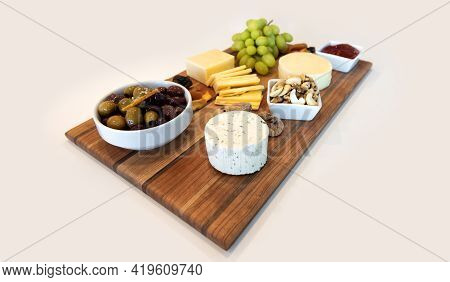 Delicious Cheese Assortment On A Wooden Board With Fruit, Nuts, Jelly, And Olives. Gourmet Charcuter