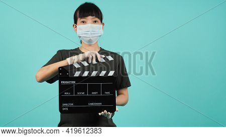 Asian Woman Wear Face Mask Hand Hold Black Clapperboard Or Movie Slate On Mint Green Or Tiffany Blue