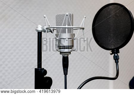 Professional Microphone On The Background Of The Light Wall. Studio Microphone For Professional Reco