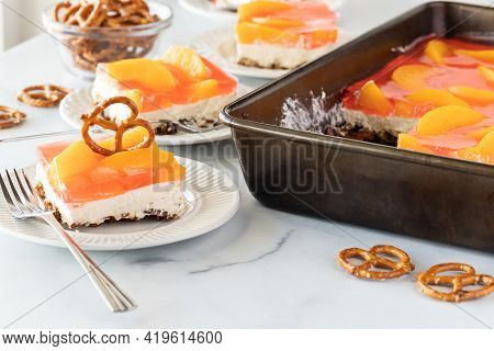 Slices Of Peach And Pretzel Jelly Dessert Against A Bright Sunny Window.