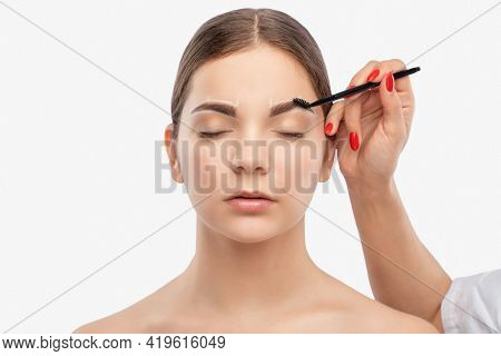 Makeup Artist Combs  And Plucks Eyebrows After Dyeing In A Beauty Salon.professional Makeup And Cosm