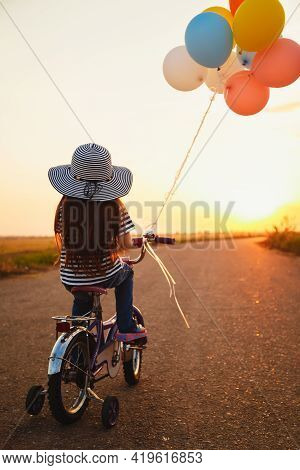 Cute Little Girl With Colorful Balloons Cycling At The Road At Sunset Sky Summer Time. Back View.