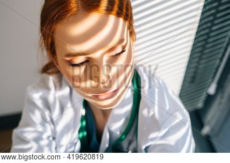 Close-up Face Of Desperated Sad Young Female Doctor In White Coat Sitting On Floor Hugging Legs With