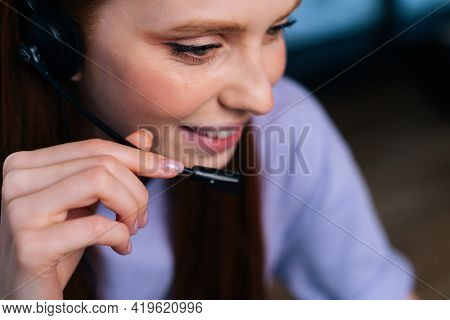 Close-up Face Of Smiling Young Woman Operator Using Headset During Customer Support At Home Office.