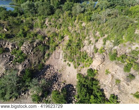 The Rocky Slopes Of The Hill Are Overgrown With Bushes And Small Trees. Rocky Terrain, Aerial View.