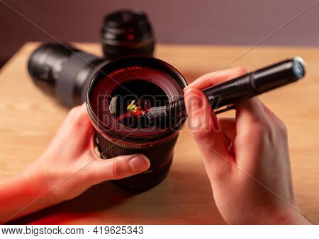 Photographer Hands Close Up Cleaning Camera Lens With Black Professional Brush, Closeup, Removing Du
