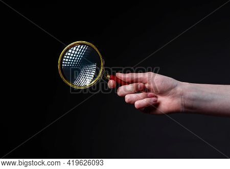 Magnifier Or Loupe In Woman Hand On Black Background. Concept Of Searching And Studying