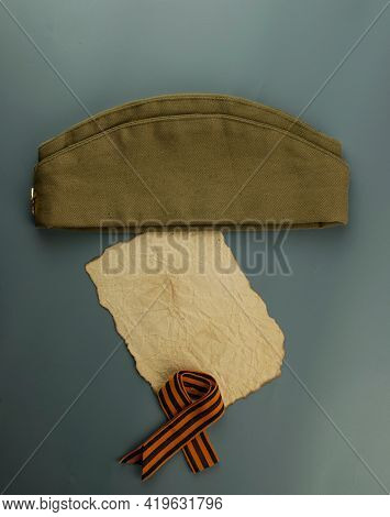 may 9 victory day holiday background. ribbon of St.George, burnt paper and military cap - traditional symbol of Victory Day 1945. greeting card design. copy space
