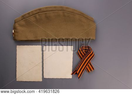 may 9 victory day holiday background. ribbon of St.George,vintage photoframe and military cap - traditional symbol of Victory Day 1945. greeting card design. copy space