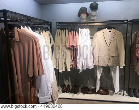 Men fashion clothes  Hanging clothes suit colorful or closet rack different coloured man suits.coat in a closet on hangers in a store