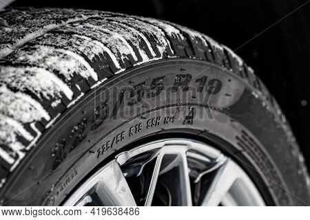 Close Up View Of Snowy Tire With Tire Width, Height And Wheel Diameter Designation. Winter Tire Size