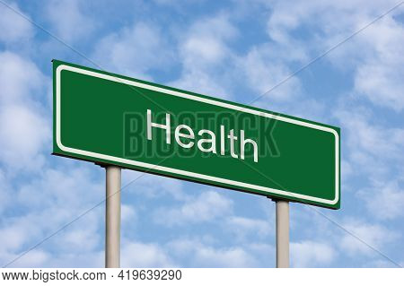 Health Care Concept, Green Signpost Road Sign, White Text, Grey Pole Posts, Blue Sky, Bright Cloudsc
