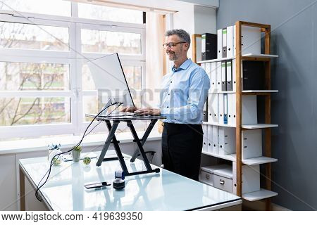 Large Version Of Adjustable Height Desk Stand In Office Using Computer