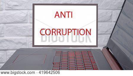 Anti Corruption Text Written On A Blackboard Hanging On A Brick Wall.