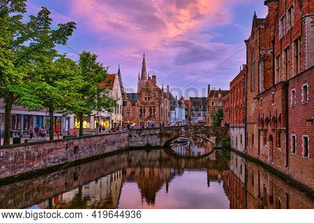 Evening dusk picturesque view of Bruges Brugge town canal with bridge and medieval houses, Belgium