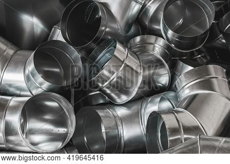 Bends Of Pipes From Galvanized Sheet Material Background. Steel Pipe Tube On Construction Site.