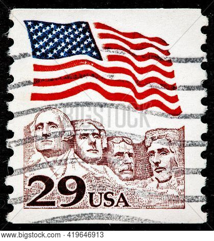 United States Of America - Circa 1991: A Stamp Printed In The Usa Shows American Flag Waving Above M