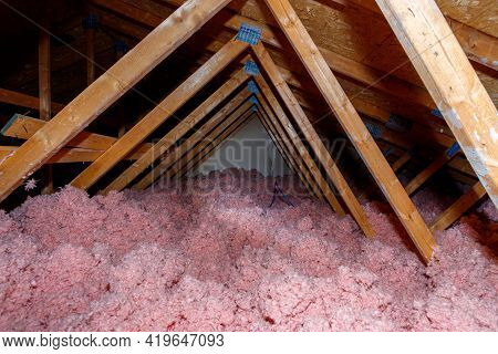 A Dark Attic In A Wood-frame House Has Pink Loose Fill Fiberglass Insulation Covering The Floor.