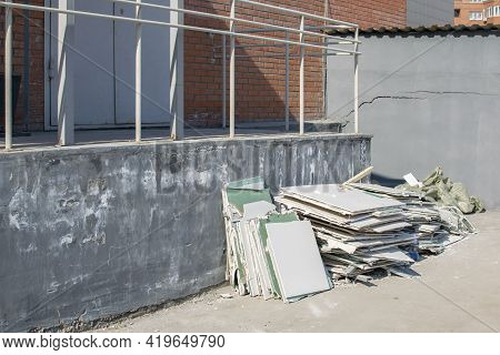A Pile Of Construction Debris, Broken Drywall, Lies Near A Brick Building In A New Area Of Residenti