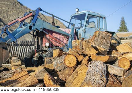 A Pile Of Sawn Wood, Chocks, Lies In The Yard On The Street In The Village Against The Background Of