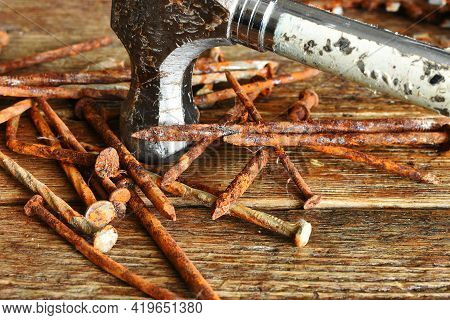 A Close Up Image Of Old Rusted Nails And Old Construction Hammer.