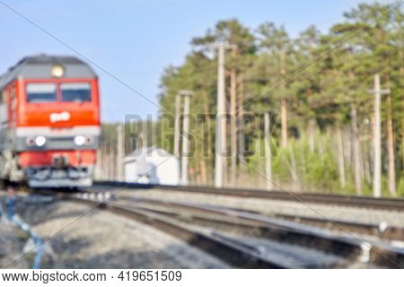 The Soft Focus Of The Red Train And Railway Against The Background Of The Green Forest And The Blue