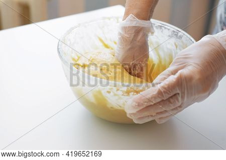 Woman Preparing Dough. Close-up Of Female Hands In Gloves Whipping, Kneading The Dough.