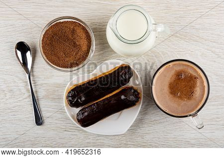 Teaspoon, Cocoa Powder With Sugar In Transparent Bowl, Pitcher With Hot Milk, Two Eclairs With Choco