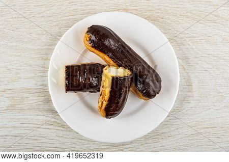 Whole Eclair With Chocolate Glaze, Halves Of Eclair In White Plate On Wooden Table. Top View