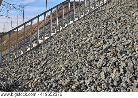 Gabion, A Metal Mesh Filled With Thick Stones. Stairs For Climbing To The Bridge