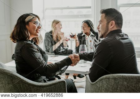 Business people shaking hands and drinking wine