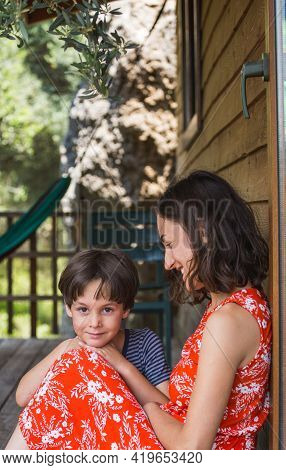Young Mother With Her Son Spend Time On The Veranda Of A Country House. Mom With A Child. Family Is