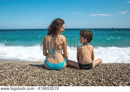 A Woman With A Child Sits On The Beach And Looks At The Sea, A Boy And His Mother Are Resting On The