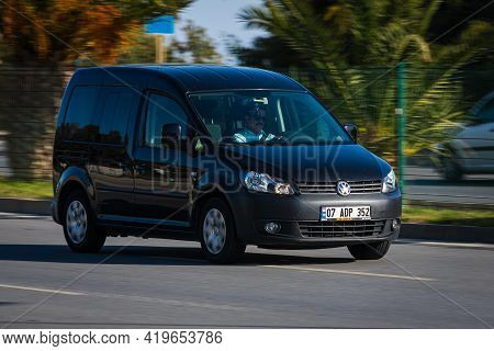 Alanya, Turkey  - April 17  2021:    Black Volkswagen Caddy Is Driving Fast On The Street On A Warm