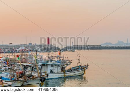 Daecheon, South Korea; April 25, 2021: Fishing Boats Docked In Seaport With Red Lighthouse In Backgr