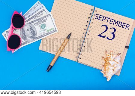 23rd Day Of September. Travel Concept Flat Lay - Notepad With The Date Of 23 September Pen, Glasses,