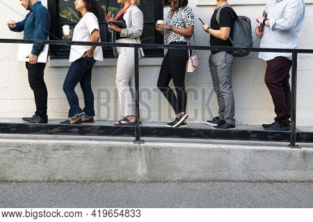 Business people holding digital devices while waiting in line