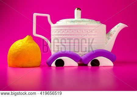 Teapot with plasticine eyes and lemon on the pink background. Cartoon plasticine parts of face on things