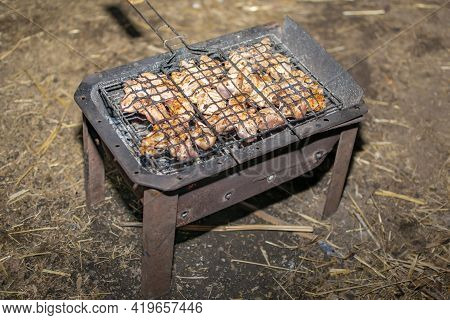 Pieces Of Fresh Meat Are Placed In A Barbecue Grill, Which Lies On A Hot Grill With Coals At Night U