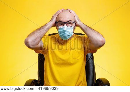 A Bald Man With Glasses And A Medical Mask Is Sitting In A Chair, His Eyes Bulging, Clutching His He