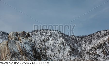 A Flat-topped Rock Devoid Of Vegetation. Cracks On The Stones. Background - Wooded Snow-covered Hill
