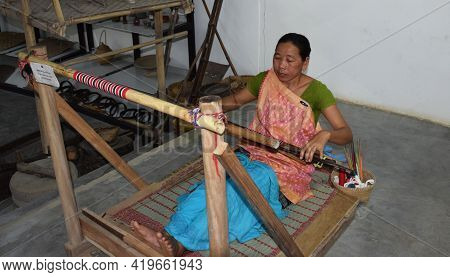 Assam - India March - 2021 A Woman Weaver Uses A Loom To Make A Hand Woven Saree At  Her Workshop.